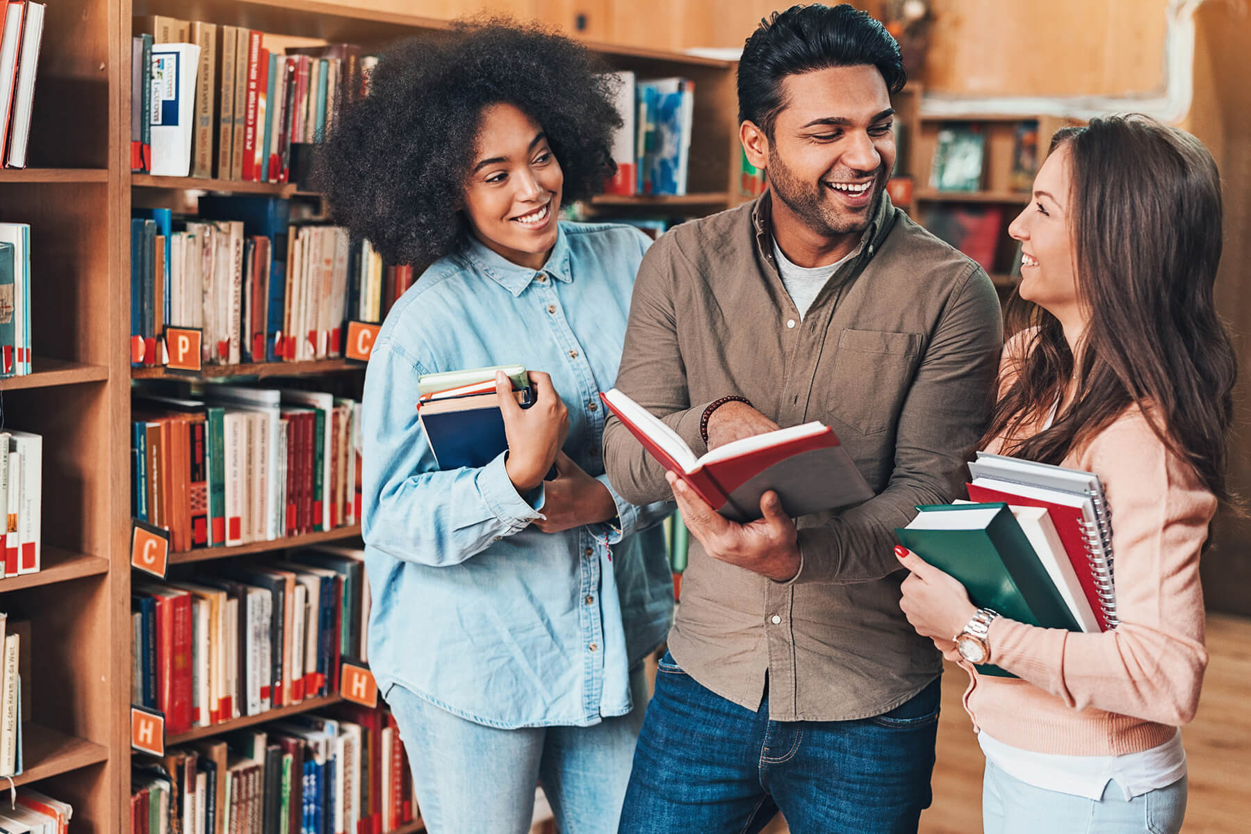 Three college students talk in a library while holding books