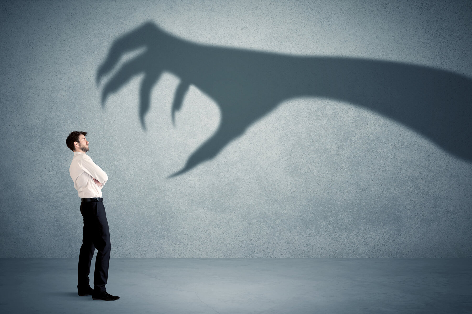 Businessman stands facing the shadow of a monster hand