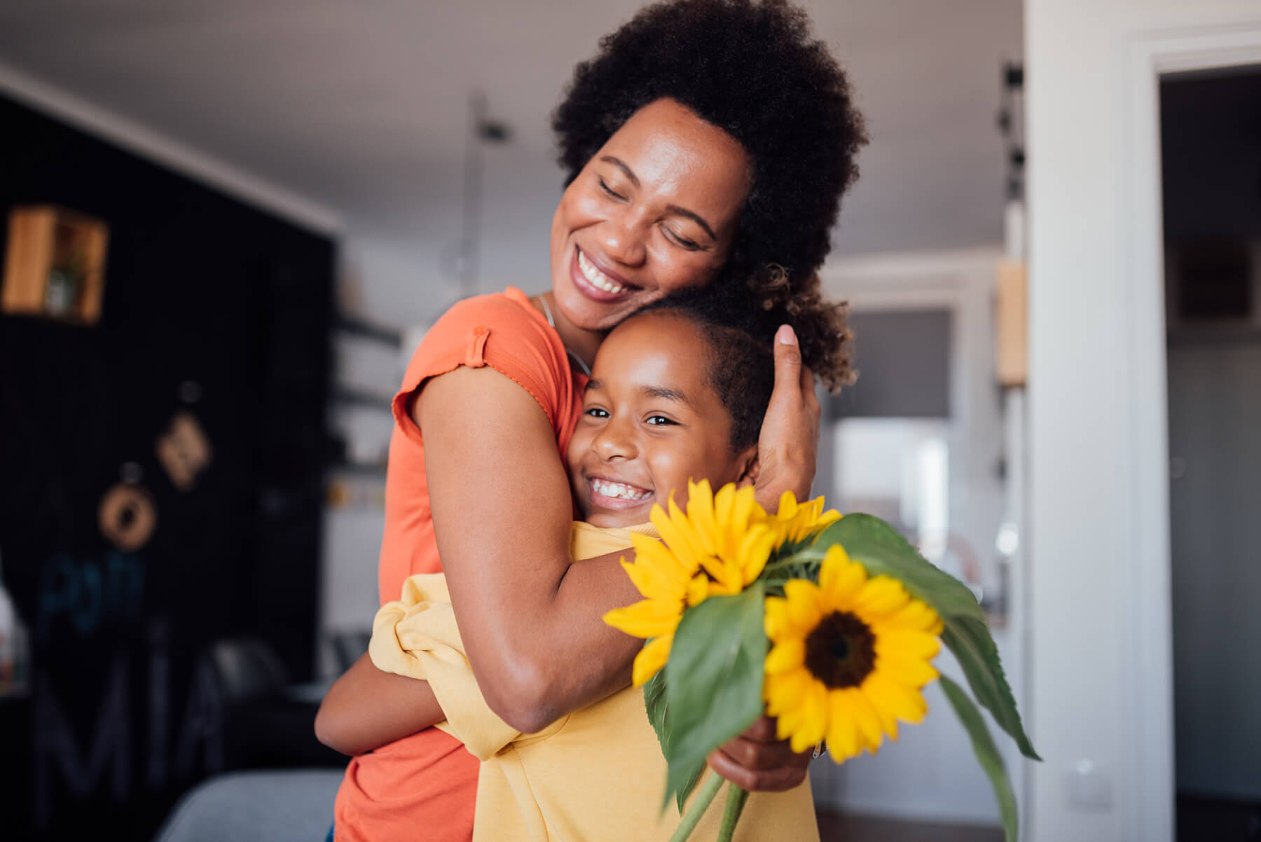 A mother and daughter embrace, holding sunflowers