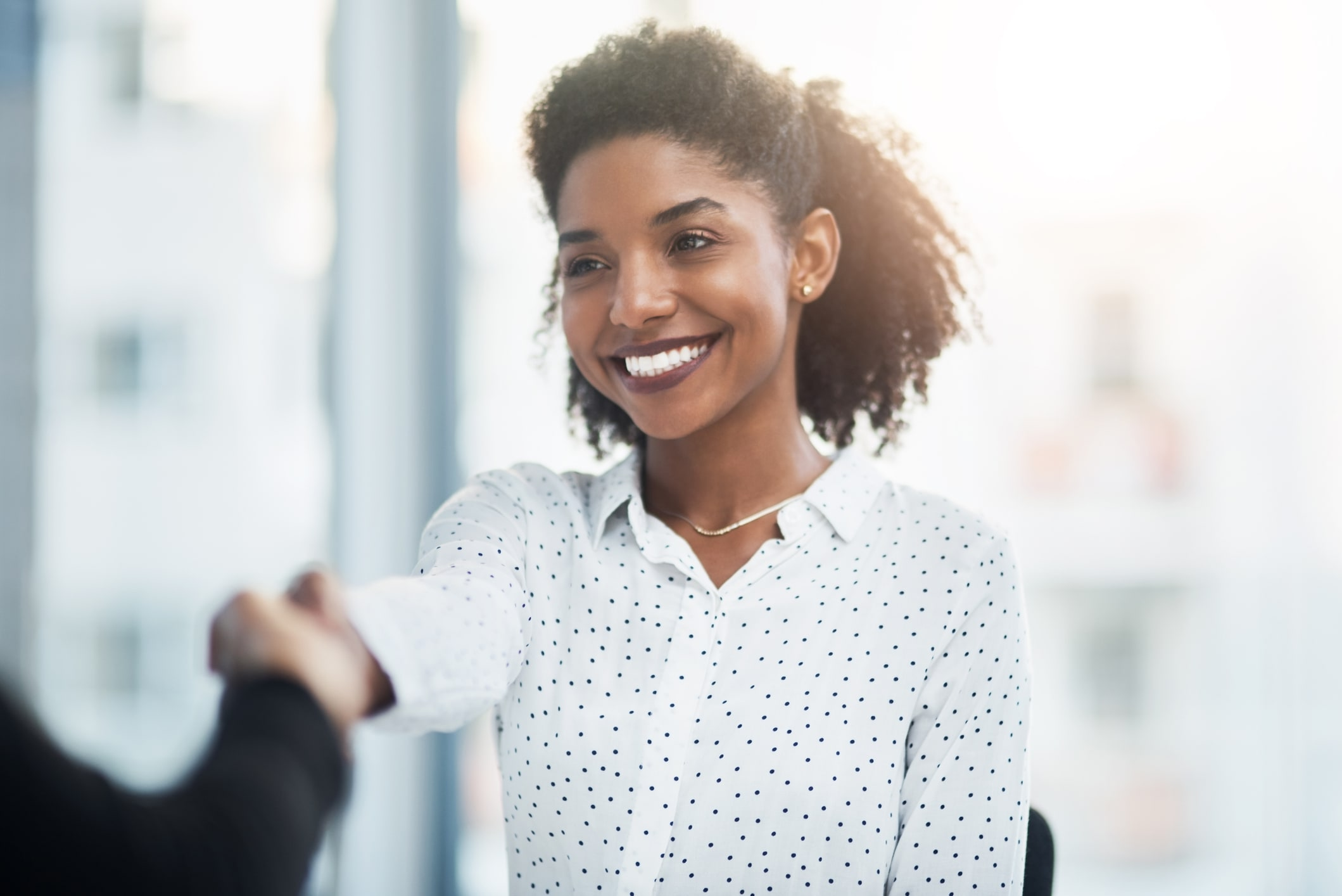Smiling young businesswoman shakes a client's hand