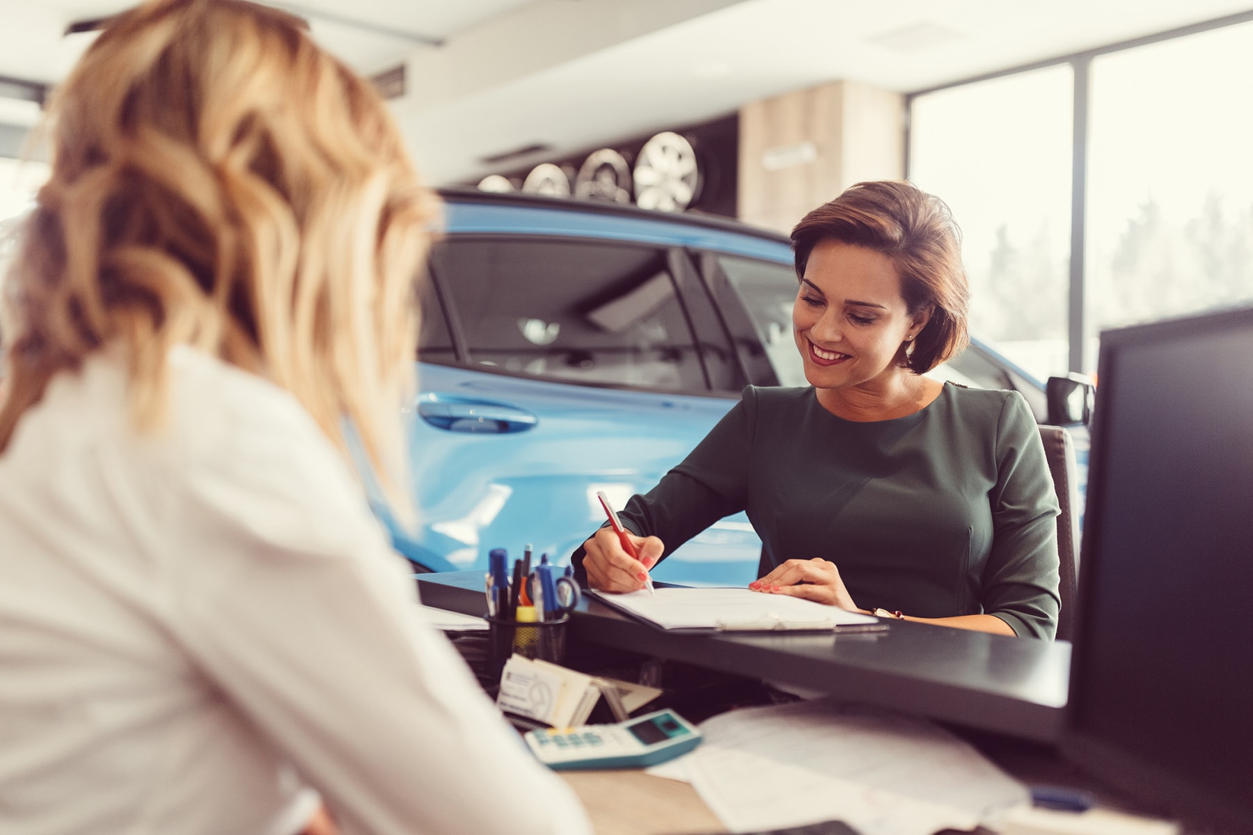 A woman fills out a loan application for a new car