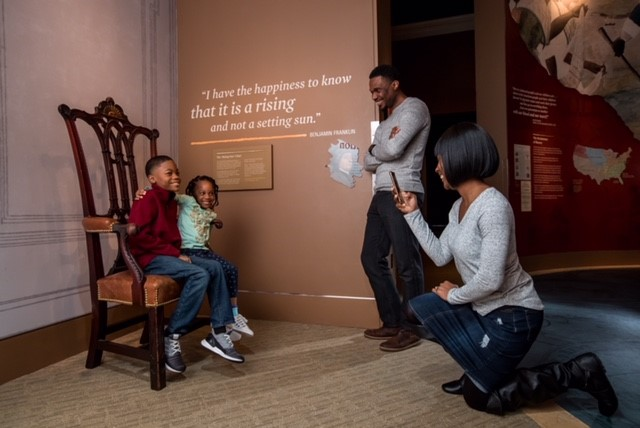Mother takes photo of her 2 children at the Museum